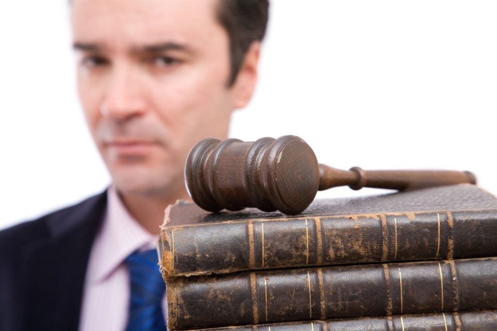 legal concept with businessman holding gavel and law books